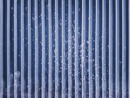 Panel de revestimiento de acero azul marino acanalado con marcas de rociado de concreto. foto