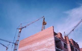 Unfinished house and yellow tower crane. photo