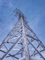 torre de alta tensión con fondo de cielo azul. foto