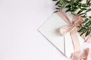 sobre sobre un fondo blanco-rosa con cinta de seda melocotón y rosa foto