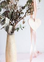 colgante de corazón de madera clara en una cinta de seda rosa. foto