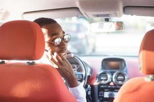 Feliz afroamericano conduciendo un coche con un teléfono, en el verano foto