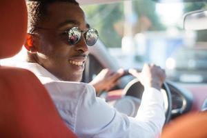 feliz afroamericano conduciendo un coche, en el verano foto