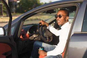 Feliz afroamericano conduciendo un coche con café, en el verano foto
