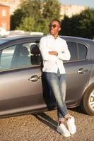 feliz afroamericano junto a un coche en el verano foto