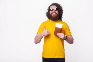 bearded  man showing thumb up gesture and passport with tickets photo