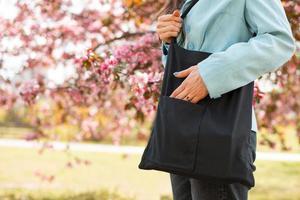 Foto de mujer con bolsa de material reutilizable en el exterior