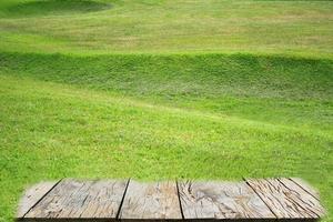 Césped de hierba verde en el jardín con piso de madera foto