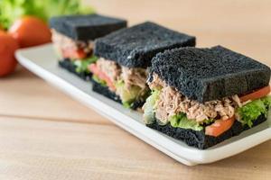 Tuna charcoal sandwich on wood table photo