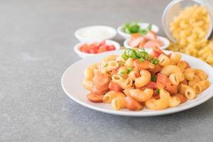 Macaroni with sausage on the table photo