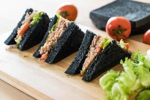 Tuna charcoal sandwich on wood board photo