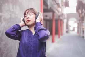 Happy young asian woman listening to music photo