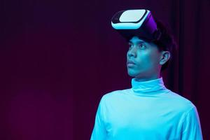 Young Asian man wearing virtual reality goggle watching 360 degree vdo photo