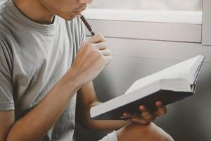 Young man reading book and thinking gesture at living room photo