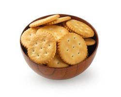Galletas cracker en tazón de madera aislado sobre fondo blanco. foto