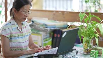 Senior woman typing on keyboard and using computer to write email video
