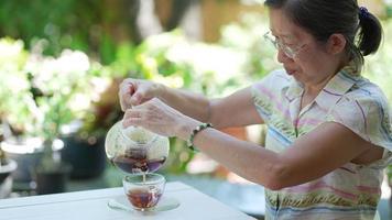 Senior asian woman drink hot black tea in garden of cafe video