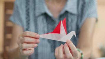 Senior woman showing bird origami after folding paper as a hobby video
