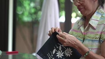 close-up vista de tecido de costura de mulher sênior para fazer bordado em casa video