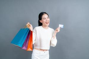 Hermosa mujer asiática con bolsas de la compra y mostrando tarjeta de crédito foto