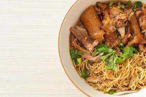 Stewed pork leg noodles in brown soup photo