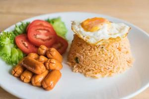 Fried rice with sausage and fried egg on the table photo
