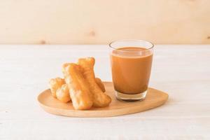Deep-fried dough stick with milk tea on wood photo