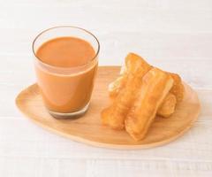 Palo de masa frita con té con leche sobre madera foto