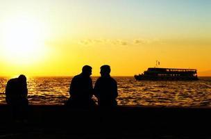 silueta de personas y el mar al atardecer foto