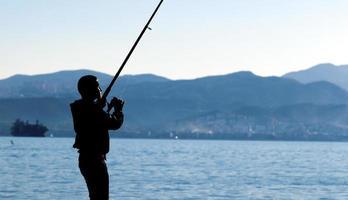 una sombra de niño cerca del mar pescando foto