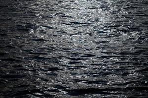 el mar oscuro y el reflejo de la luz del sol foto