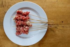 Raw goat satay on white plate with wooden table photo