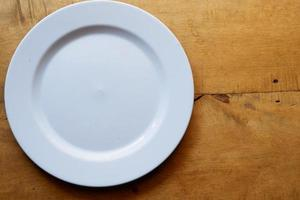 White plate on wooden table with copy space photo