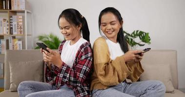 meninas gêmeas brincando no smartphone na sala de estar video