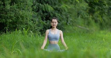 mulher fazendo ioga meditando e posicionando-se na árvore ao ar livre video