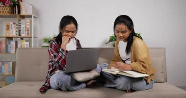 Twin Girls Reading a Book and Looking on A Laptop video
