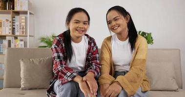 jumelles, agitant la main, assise sur un canapé video