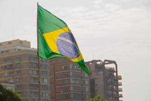 Brazil flag outdoors with buildings in the background photo