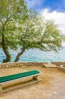Mediterranean landscape with trees and bench Novi Vinodolski Croatia. photo