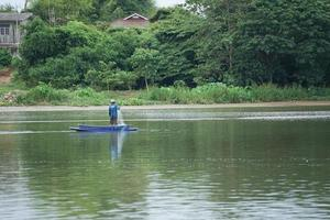 Lonely man stands on the boat and collects the fish from the net photo