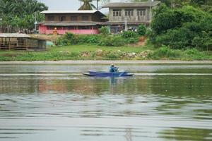 Lonely man sits in the boat and collects the fish from the net photo
