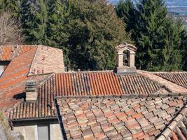 Little bell tower on the tiled roof of an Italian former convent photo