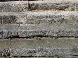 Stone steps frontally. Spring grass between stone slabs, close up photo