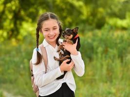 colegiala y chihuahua en la naturaleza. mascota y niña foto