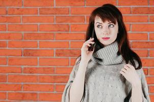 A pretty girl talking by cellphone, surprised eyes, in gray pullover photo