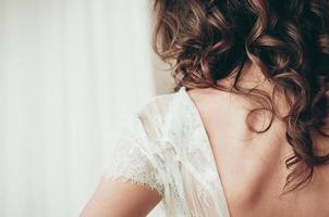 Una novia morena con vestido blanco, una vista de cerca desde la parte de atrás foto
