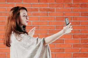 A pretty girl is making selfie with smartphone, sending air kiss photo