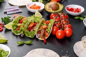 Mexican tacos with beef, tomatoes, avocado, onion and salsa sauce photo