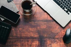 taza de café, computadora portátil, libro, teléfono inteligente en el escritorio. foto