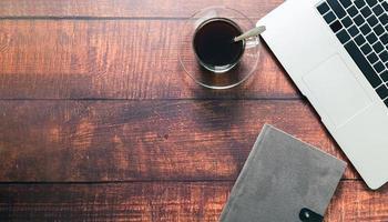 taza de café, computadora portátil, libro en el escritorio. foto
